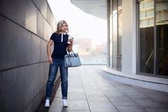 Blondes gehendes Mädchen die Straße mit Kaffee zum Mitnehmen Lizenzfreie Stockfotos