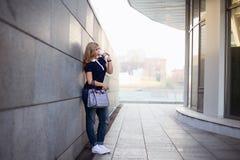 Blondes gehendes Mädchen die Straße mit Kaffee zum Mitnehmen Stockfotografie