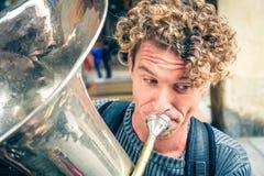 Blondes gelocktes behaartes Straßenmusikerposauneblasinstrumentausführendporträt Stockfotos
