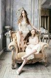 Blondes gelocktes Frisurmädchen der hübschen Zwillingsschwester zwei im Luxushausinnenraum zusammen, reiche Konzeptnahaufnahme de Lizenzfreies Stockbild