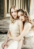 Blondes gelocktes Frisurmädchen der hübschen Zwillingsschwester zwei im Luxushausinnenraum zusammen, reiches Konzept der jungen L Stockfotos