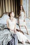 Blondes gelocktes Frisurmädchen der hübschen Zwillingsschwester zwei im Luxushausinnenraum zusammen, reiches Konzept der jungen L Lizenzfreie Stockfotografie