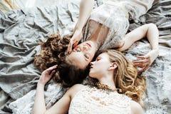Blondes gelocktes Frisurmädchen der hübschen Zwillingsschwester zwei im Luxushausinnenraum zusammen, reiches Konzept der jungen L Lizenzfreies Stockfoto