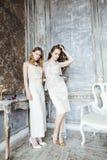 Blondes gelocktes Frisurmädchen der hübschen Zwillingsschwester zwei im Luxushausinnenraum zusammen, reiches Konzept der jungen L Lizenzfreies Stockbild