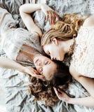 Blondes gelocktes Frisurmädchen der hübschen Zwillingsschwester zwei im Luxushausinnenraum zusammen, reiches Konzept der jungen L Lizenzfreie Stockfotos