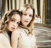 Blondes gelocktes Frisurmädchen der hübschen Zwillingsschwester zwei im Luxushausinnenraum zusammen, reiches Konzept der jungen L Stockbilder