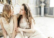 Blondes gelocktes Frisurmädchen der hübschen Zwillingsschwester zwei im Luxushausinnenraum zusammen, reiches Konzept der jungen L Stockfoto