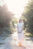 Blondes gelocktes Haar des netten schönen Mädchens, das im Wald in ein Hochzeitskleid in der Sonne bei Sonnenuntergang geht Lizenzfreies Stockfoto