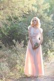 Blondes gelocktes Haar des netten schönen Mädchens, das im Wald in ein Hochzeitskleid in der Sonne bei Sonnenuntergang geht Lizenzfreie Stockbilder