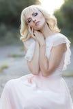 Blondes gelocktes Haar des netten schönen Mädchens, das im Wald in ein Hochzeitskleid in der Sonne bei Sonnenuntergang geht Lizenzfreies Stockbild