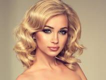 Blondes gelocktes Haar des reizend Mädchens Stockfoto