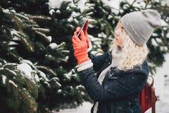 Blondes gelocktes Mädchen, das Foto auf Smartphone, Winter macht stockfotografie