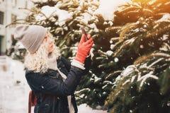 Blondes gelocktes Mädchen, das Foto auf Smartphone, Winter macht lizenzfreie stockfotografie