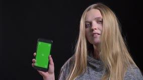 Blondes gerad-haariges Mädchen, das grünen Schirm von Smartphone demonstriert, um den App über schwarzen Hintergrund ernsthaft stock footage