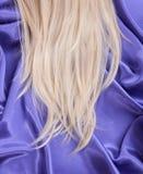 Blondes gerades Haar auf blauem silk Gewebe Stockfoto