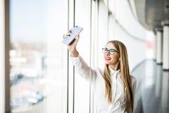 Blondes Geschäftsfrau-Nehmen selfie am Telefon im modernen Büro Lizenzfreie Stockfotografie