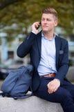 Blondes Geschäftsmannsitzen äußer und Unterhaltung am Telefon Lizenzfreie Stockfotografie