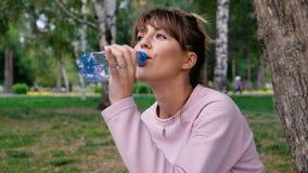 Blondes Getränkwasser des attraktiven Mädchens mit Vergnügen draußen Eine junge Frau trinkt Trinkwasser von einer Plastikflasche stock footage