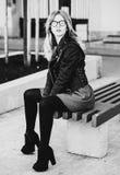 Blondes gir sitzt auf einer Bank, Sommerstadt, Schwarzweiss-Bild Stockfotos