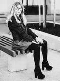 Blondes gir sitzt auf einer Bank, Sommerstadt, Schwarzweiss-Bild Stockbilder