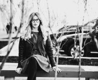 Blondes gir sitzt auf einer Bank, Sommerstadt, Schwarzweiss-Bild Stockfotografie