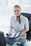 Blondes glückliches Geschäftsfrauschreiben im Tagebuch Stockbilder