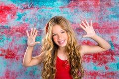 Blondes glückliches Kindermädchen in den roten glücklichen Armen oben Lizenzfreie Stockfotos