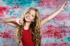 Blondes glückliches Kindermädchen in rotem glücklichem mit den Armen oben Stockbild