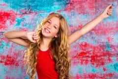 Blondes glückliches Kindermädchen in rotem glücklichem mit den Armen oben Lizenzfreie Stockfotografie