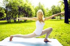 Blondes glückliches lächelndes Mädchen, das Yoga im Park, Lebensstilsport-Leutekonzept tut Stockbilder