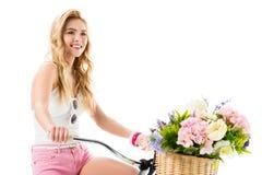 Blondes glückliches Mädchenreitfahrrad mit Blumen im Korb Stockbilder