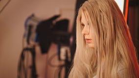 Blondes hübsches junges Modell im Cocktailkleid, das für Fotografen aufwirft - arbeiten Sie Bühne hinter dem Vorhang um Stockbild