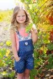 Blondes hübsches Kindermädchen im Traubenweinberg Stockfotos