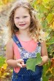 Blondes hübsches Kindermädchen im Traubenweinberg Lizenzfreie Stockbilder