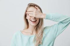 Blondes hübsches Mädchen, das ihre Augen mit der Hand, den glücklichen Ausdruck habend schließt und breit lächeln und nehmen vorw Stockbild