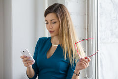Blondes hübsches Mädchen im Büro hält Gläser und das Schauen zum Smartphone Stockfotos