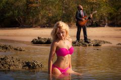 Blondes hübsches Mädchen im rosa Badeanzug sitzen in flachem Lizenzfreies Stockbild