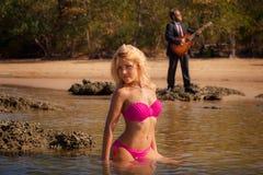 Blondes hübsches Mädchen im rosa Badeanzug sitzen in flachem Stockfotografie