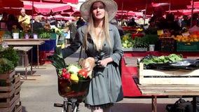 Blondes hübsches Mädchen mit Fahrrad geht am Markt stock video footage