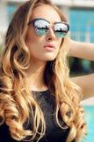 Blondes Haar der herrlichen Frau im eleganten Kleid, das neben Swimmingpool aufwirft Lizenzfreie Stockfotografie