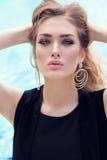 Blondes Haar der herrlichen Frau im eleganten Kleid, das neben Swimmingpool aufwirft Lizenzfreies Stockfoto