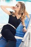 Blondes Haar der herrlichen Frau im eleganten Kleid, das neben Swimmingpool aufwirft Lizenzfreie Stockfotos