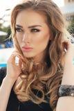Blondes Haar der herrlichen Frau im eleganten Kleid, das neben Swimmingpool aufwirft Stockbilder