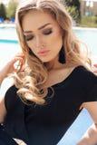 Blondes Haar der herrlichen Frau im eleganten Kleid, das neben Swimmingpool aufwirft Stockfoto