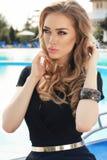 Blondes Haar der herrlichen Frau im eleganten Kleid, das neben Swimmingpool aufwirft Stockfotografie