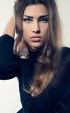 Blondes Haar der jungen attraktiven Frau im schwarzen Kleid, das betrachtet, kam Lizenzfreies Stockbild