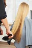 Blondes Haar Friseur, der langes blondes Haar im Salon kämmt Lizenzfreie Stockbilder