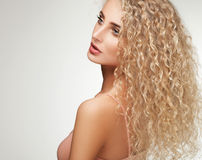 Blondes Haar. Schönheit mit dem gelockten langen Haar. Stockbilder