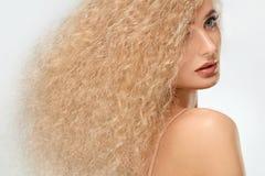 Blondes Haar. Schönheit mit dem gelockten langen Haar. Hohe Qualität Lizenzfreies Stockbild