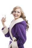 Blondes haooy Mädchen in trinkendem Champagner des Bademantels Stockfotografie